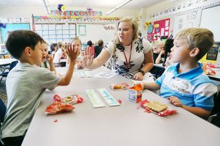 Rockne Roll/News-Register##Newby Elementary School kindergartner Maddox Schmidt high-fives teacher Rachel Sundquist as the class wraps up breakfast on the first day of school Tuesday. Sharing a bite to eat served as a way to ease into the first day of school.
