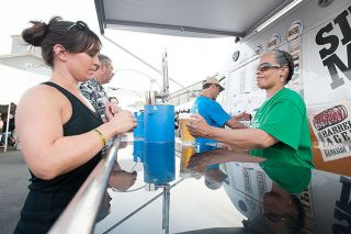 News-Register file photo##Oregon Brews & BBQs volunteer Olivia Scales serves a Silver Moon beer to Leslie Plotts at last year's festival in McMinnville's Granary District.