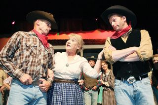 "Rockne Roll/News-Register##""Everything's up to date in Kansas City,"" sings Will (Robert Salberg, right) in a number featuring fellow cowboys (such as Erik Svec, left) and Aunt Eller (Pam Harris)."