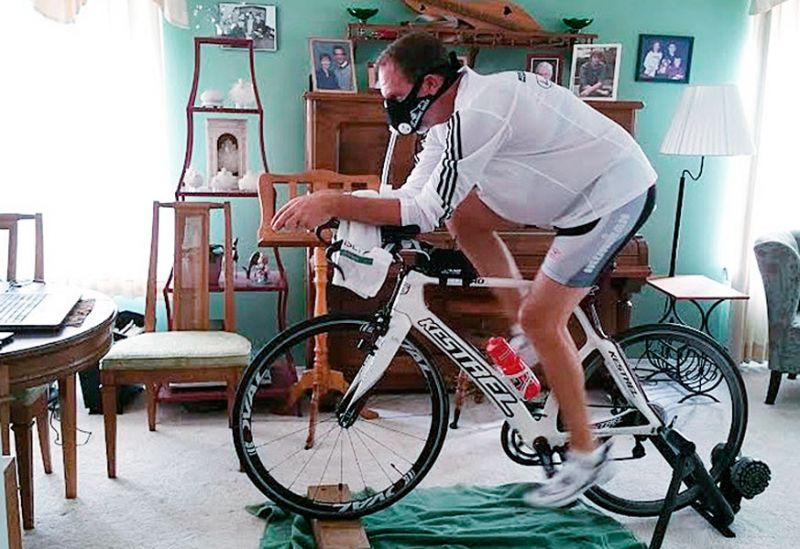 Marcus Larson/News-Register##Art Bradley trains on a stationary bike while watching a video of the Hawaii Ironman course. He wears a special mask that restricts air flow to strengthen his diaphragm. He's hoping it will help prepare him for Hawaii's high humidity.