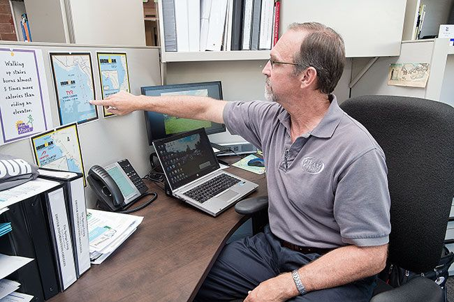 Marcus Larson/News-Register##Art Bradley keeps maps of the Ironman routes posted at his desk at the headquarters of The Springs Senior Living, where he is the employee wellness coach.