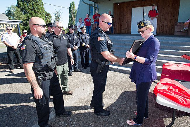 Marcus Larson / News-Register##Renee Ohler, right, commandeer of Carlton Memorial American Legion Post 173, shakes hands with Yamhill Police Officer Travis VanCleave, backed by Chief Greg Graven and Officer David Thiems, as she presents a plaque honoring their service. The Post also honored Carlton police and Yamhill and Carlton firefighters on the 9/11 anniversary.