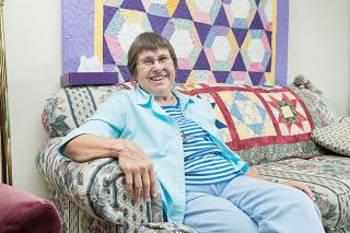 Marcus Larson/News-Register##Donna Hulett enjoys displaying her quilts at home. An equilateral triangle quilt hangs on the wall behind her. A challenge quilt, featuring blocks made by several friends, is on the sofa back.