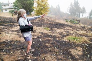 Marcus Larson/News-Register##Kathleen Shaughnessy points out where the fire moved through her backyard, nearly reaching her house on Mountain Top Road.