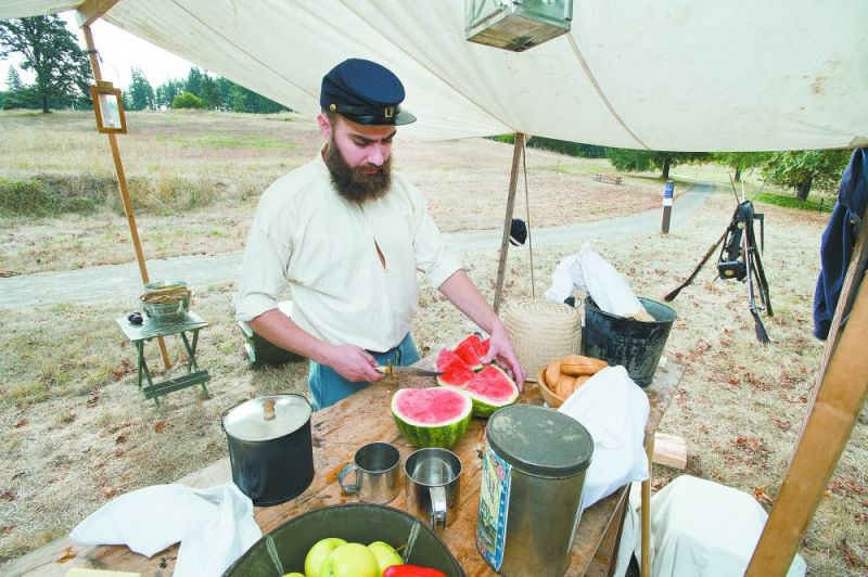"Marcus Larson/News-Register##Re-enactor Andrew Engel, portraying a soldier stationed at the Fort Yamhill garrison, works in the ""kitchen,"" slicing watermelon for the rest of his unit. The demonstration was part of a twice-yearly history day event at the state heritage area near Grand Ronde."