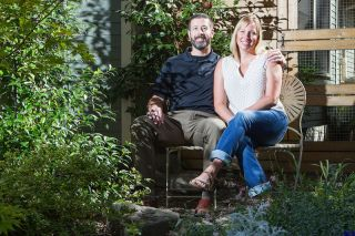 Rockne Roll/News-Register##Eric and Carly Baughman, pictured in their Yard of the Month-winning front yard in McMinnville Wednesday, Sept. 13. Carly says maintaining the front and back yards takes over two hours of hand watering each day.