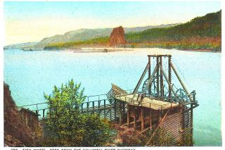 ##A hand-tinted postcard image of a fish wheel on the upper Columbia River with Beacon Rock in the background, circa 1920.