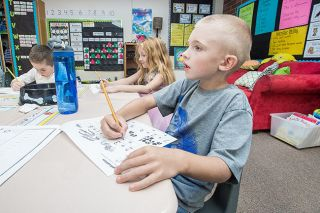 "Marcus Larson/News-Register##Wascher Elementary School first-grader Henry Spencer practices writing numbers as he shows his work during math class. The school has adopted the theme ""Love of Learning"" for the first quarter of the year."