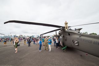 Marcus Larson/News-Register file photo##Chief Warrant Officer 2 Mike Newgard stands on his unit's Blackhawk helicopter for a better view during last year's Oregon International Air Show at the McMinnville Airport.