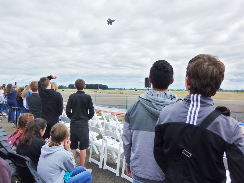 Starla Pointer / News-Register##Eighth-graders watch an F-35 fighter jet make a slow pass in front of the crowd.