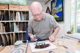Marcus Larson/News-Register##In the studio at his McMinnville home, Ralph Kraft uses a soldering iron to fuse together colored glass sections of a pig. Once the solder cools, the portrait is like one piece, he said.