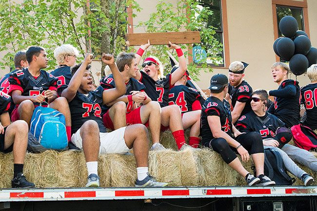 Marcus Larson / News-Register##Members of the McMinnville High School football team cheer as they ride down Third Street Thursday afternoon. They will compete againgst Centennial High School players tonight.