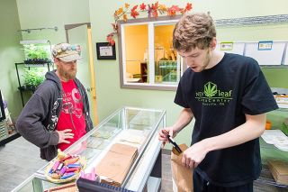 Marcus Larson/News-Register##Steven Perkins purchases some marijuana from Jerod Bogh of New Leaf in McMinnville. Oct. 1 was the first day of legal recreational marijuana sales. Possession of marijuana was made legal July 1.