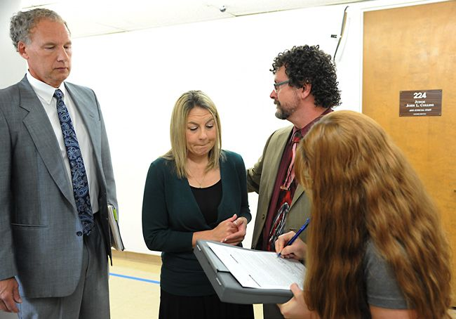 Rusty Rae / News-Register##Attorney Walter Todd stands with his client, Jennifer Weathers, center, as a woman from the pretrial release office explains Weathers  release agreement following her appearance in court Wednesday afternoon.