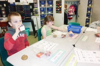 Starla Pointer/News-Register##Third-graders Aiden Schwab and Sophia Bliss enjoy eating at their desks on the second day of the Breakfast in the Classroom at Columbus Elementary School.