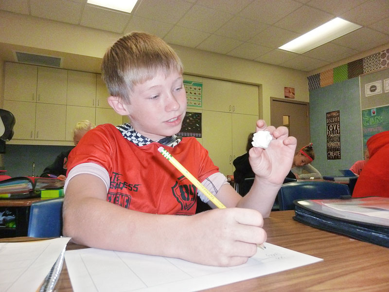 Starla Pointer/News-Register##In Bobbi Kidd's sixth-grade class at YCIS, Devin Ellis examines a marshmallow as he writes descriptive words. Kidd asked students to be as descriptive as possible in order to bring their writing alive.
