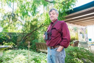 Marcus Larson/News-Register##Former TV journalist Harry Fuller, above in his McMinnville backyard, is a birdwatcher and author of two books with collaborator Peter J. Thiemann. Their most recent focuses on the great gray owl.