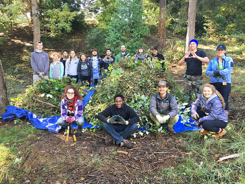 Submitted photo##Local community members and students from Linfield College and Chemeketa Community College pose with a pile of invasive weeds removed from along Cozine Creek on Linfield Campus. Linfield is working with the Greater Yamhill Watershed Council to secure grant funding to enhance the habitat on Cozine Creek on campus, and to engage the community in service learning activities.