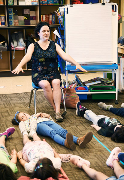 "Rusty Rae/News-Register##Leading a mindfulness session, Fleckenstein encourages students to relax. Teaching meditation skills to children ""brings meaning and purpose to my life,"" she said."