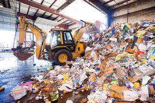 Marcus Larson/News-Register file photo##Recology worker Marcelino Ramirez uses a backhoe to sort a pile of waste, much of it contaminated recyclables, at the company's McMinnville facility.