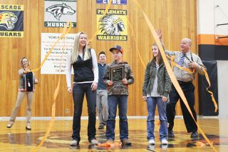 Rockne Roll / News-Register##Principal Greg Neuman honors the winning Y-C FFA ag sales team, Elsie Duyn, Ryan Berhorst and Abbey Berhorst, at an assembly Tuesday.  Liberty Greenlund, a 2016 Y-C High graduate, also went to the national competition.