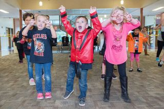 Marcus Larson/News-Register##Peyton Zook, dressed as Michael Jackson, and other first graders, practice their scary zombie poses as they practice for the upcoming Thriller dance at the McMinnville High School football game on Friday.