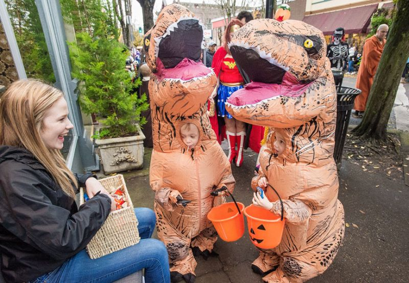 Marcus Larson/News-Register##Twin brothers Everett and Easton Edgerly, dressed as dinosaurs, receive candy from Twist employee Hanna Dobash as they trick or treat on Third Street during the McMinnville Downtown Association's Safe and Sane Halloween on Monday.