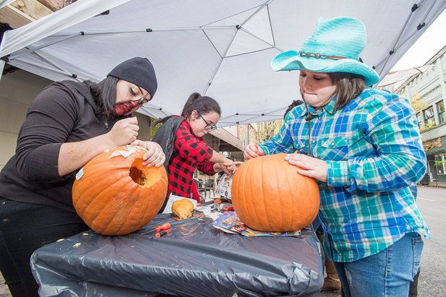 Marcus Larson/News-Register##From left, Yenifer Marin, Lisbeth Marin, and Makayla Anderson carve pumpkins at the McMenamins Hotel Oregon booth during Third Street trick-or-treating.