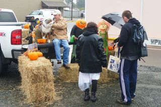 Paul Daquilante / News-Register##Rolly Heuser, owner of Coyote Joe s in Willamina, hands out candy to locals from the bed of his truck during the  Trunk of Treat  event on Halloween.