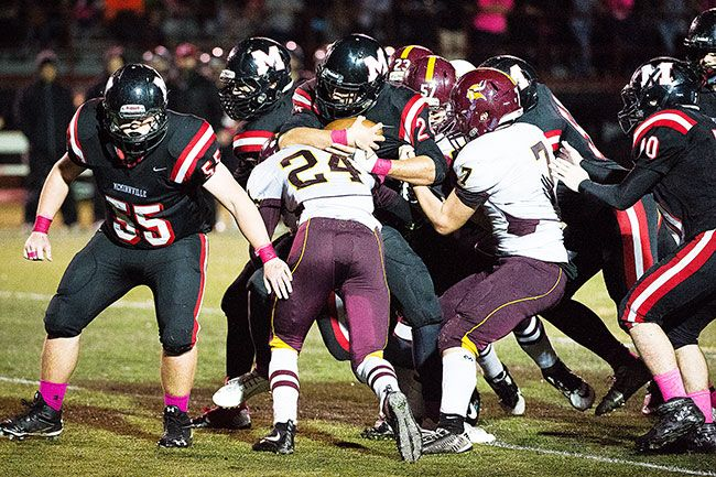 Marcus Larson/News-Register##McMinnville junior Cedric Agcaoili-Ostrom is stopped by Forest Grove senior A.J. Turner during the Grizzlies  28-20 loss to the Vikings Friday night at Wortman Stadium.