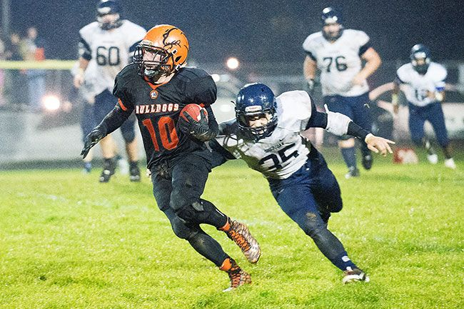 Marcus Larson/News-Register##Willamina sophomore Ian Bruckner (10) advances the ball with Sheridan s Chase Butt (35) in pursuit Friday evening at Glen Larkin Field. The Bulldogs attained their first win of the season against the Spartans, 22-12.
