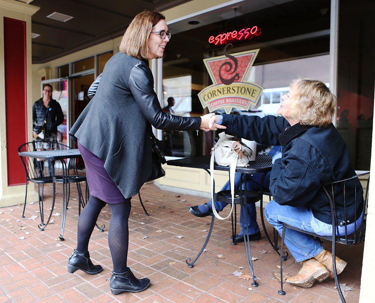 Rockne Roll / News-Register##Oregon Gov. Kate Brown shakes hands with Linda Kelly of Dayton in front of Cornerstone Coffee Roasters in McMinnville. The governor, who is running for election, stopped in McMinnville Friday for a campaign event.