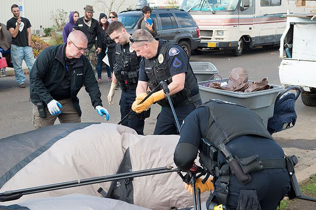 Rusty Rae/News-Register##McMinnville police Capt. Tim Symons, Officer Justin Brenner, Officer Robert Harmon and Officer Mike Maierhofer confiscate Kim Wood's tent Wednesday on N.E. Dustin Court.