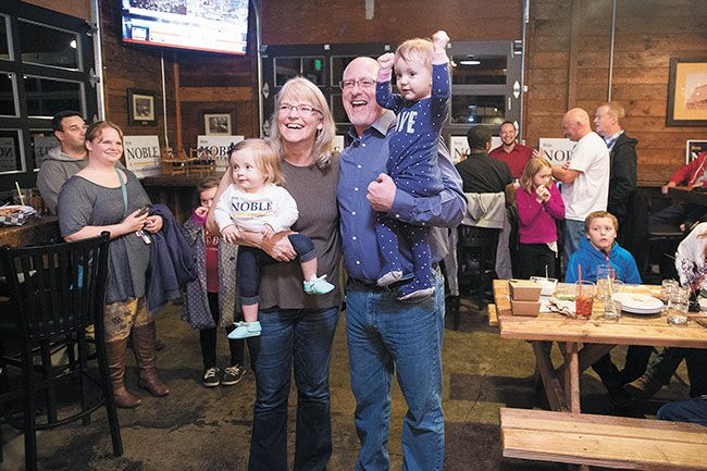 Marcus Larson/News-Register##Ron Noble and his wife, Sue, holding two of their grandchildren, react to the initial elections results that show him with a healthy lead in the race for Oregon House District 24.