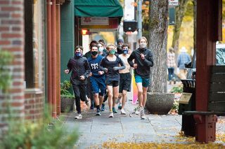Marcus Larson/News-Register##Members of the McMinnville High School cross country team jog on Third Street wearing masks last month. School board members praised the students and their coaches for taking safety precautions as they return to practices. Other fall sports teams and those from winter and spring also are practicing skills and teamwork one or two afternoons a week.
