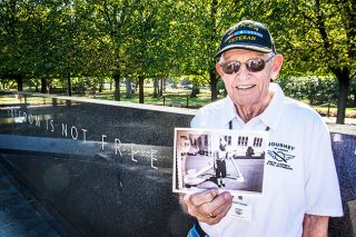 Submitted photo##During his visit to Washington, D.C., memorials, McMinnville's Ken Vronman holds a photo of himself from his Coast Guard days in the Korean War era. His ship sailed waters off Korea, predicting the weather.