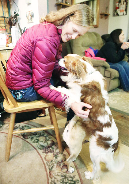 Rockne Roll/News-Register##Charlotte Goddard, a friend of Yamhill County Pet Heroes founder Kimball Kiess, pets Tucker, a rescued King Charles Cavalier Spaniel, at Kiess  home in McMinnville.