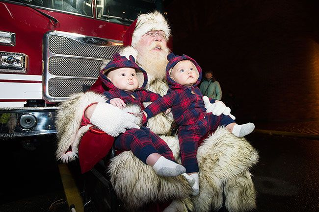 Marcus Larson / News-Register##After the parade, Santa poses with twins Merrick and Ledger Shelton.