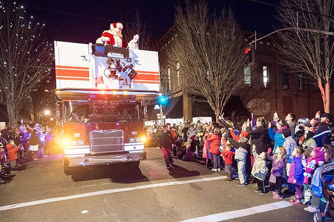 Marcus Larson/News-Register##Santa waves at parade goers as he travels down Thrid Street during the annual Christmas parade.