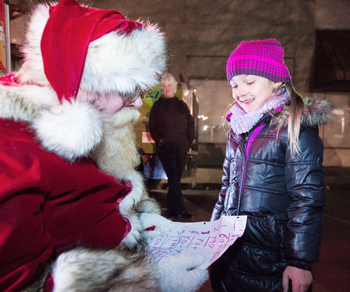 Marcus Larson/News-Register##Della Kiger happily presents Santa with her list of what she wants for Christmas.  Among them, a scooter, a pet cat, a pet rat and a yo-yo.