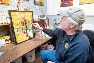 Marcus Larson/News-Register##Artist John Stromme makes some finishing touches to his latest painting.