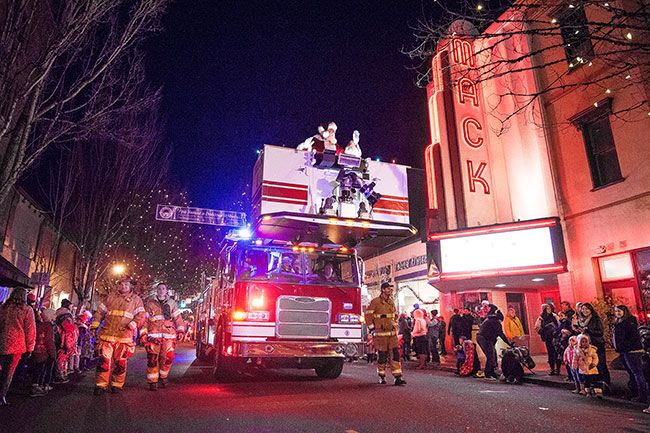 Marcus Larson / News-Register####A McMinnville fire truck carries Santa and Mrs. Claus during the annual holiday light parade.