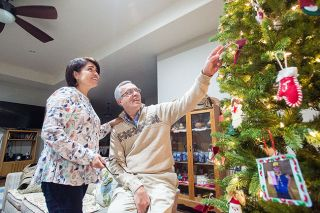 Marcus Larson/News-Register##Angel and Isabel Aguiar discuss the various homemade ornaments adorning their tree, including ones featuring childhood pictures of their kids.