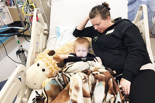 Submitted photo##Cassylou Miller of Yamhill watches her son, Brody, play with an electronic device while in Doernbecher Children's Hospital. Brody, 5, is being treated for leukemia.