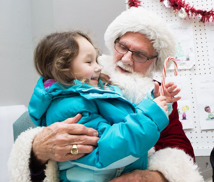 News-Register file photo##Santa visits with a youngster during his stop in Willamina in early December. On Christmas Eve, children usually do t see him -- he flies all over the world, so he stops at each home only long enough to deliver gifts and munch on cookies.