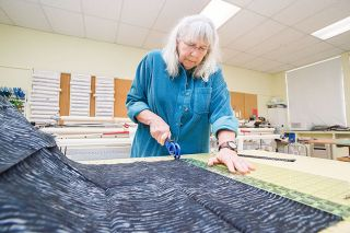 Marcus Larson/News-Register##Coastal Hills Quilter Cris Darr cuts fabric for a new quilt. She's one of the original members of the group, which recently celebrated its 20th anniversary.