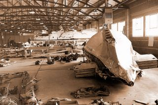 Image: FBI##Investigators carefully collected the wreckage of Flight 629 and arranged it in a Denver warehouse. The large piece in the foreground is the airliner's tail section, which was blown clean off the fuselage by the blast; the rudder has been removed so the piece would fit through the warehouse door.