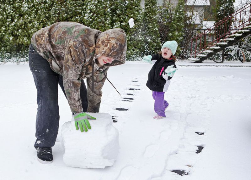 Rockne Roll/News-Register##Michael Cook works to roll up the base of a snowman as 3-year-old Scarlett Rickert lobs a snowball at him Thursday.