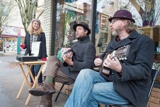Marcus Larson/News-Register##Amber Hayes, left, performs near the corner of Third and Cowls streets in McMinnville with Dusty Daleo and Yusuf Kilgore, fellow members of the Speakeasy Jazz Cats. Hayes said she hopes to earn enough money through street performing to return to New Orleans.