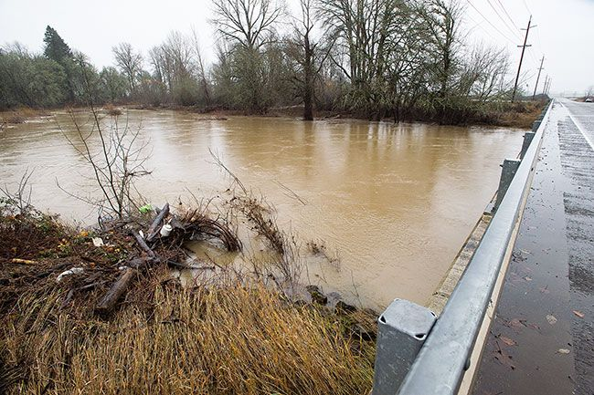 Marcus Larson/News-Register##High and dark waters swirl under the Bellevue Bridge west of Amity. Usually small Salt Creek has been transformed, like many local waterways, by heavy and persistent rains. The National Weather Service predicts the rains to continue for the next week.